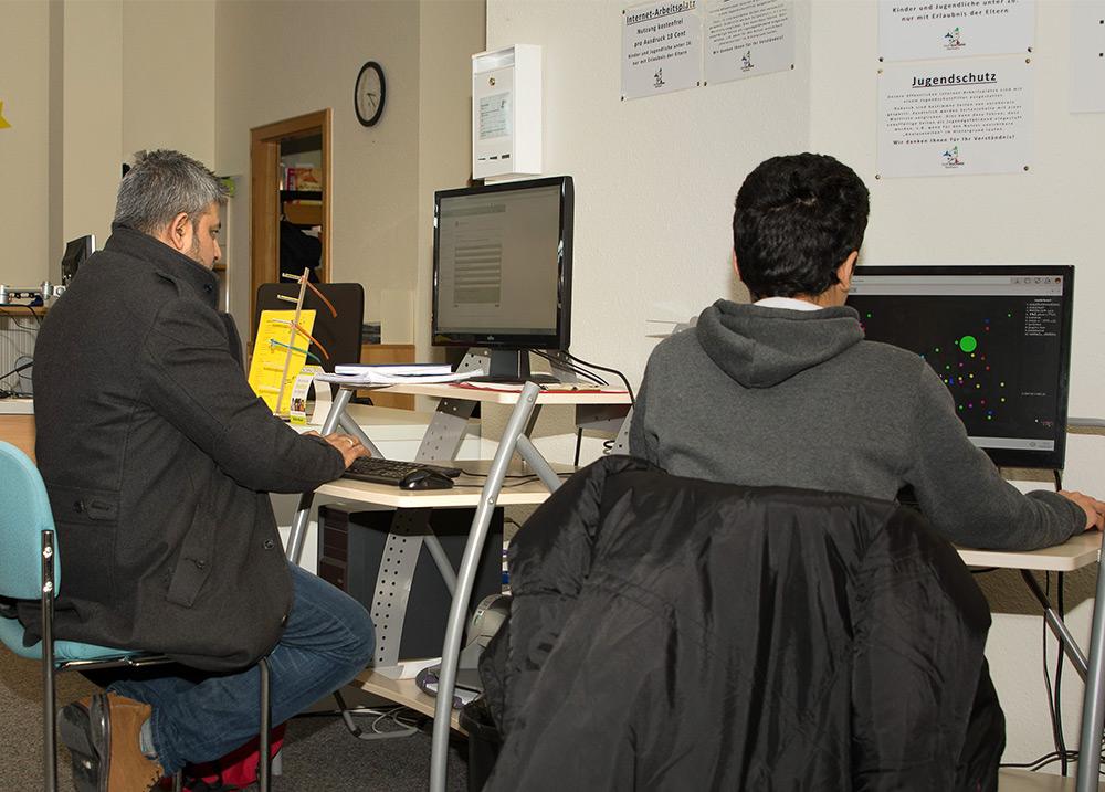 Kunden sitzen vor Computer, Internetarbeitplatz