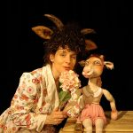 Schauspielerin verkleidet als Geisslein mit Blume und Theaterpuppe Geisslein