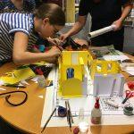 Mädchen bauen aus Papier ein Modell des Jugendbereichs der Stadtbücherei