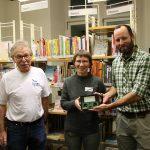 Drei Personen vor Bücherregal, zwei Männer, eine Frau, Übergabe eines Messgerätes