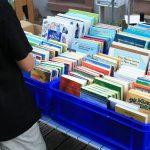 Person steht vor blauen Kisten, die verschiedene Bücher enthalten