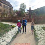 3 Kinder, das mittlere mit Fotoapparat, im Garten des Klosters Bronnbach