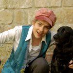 Schauspielerin vor Mauer mit Hund