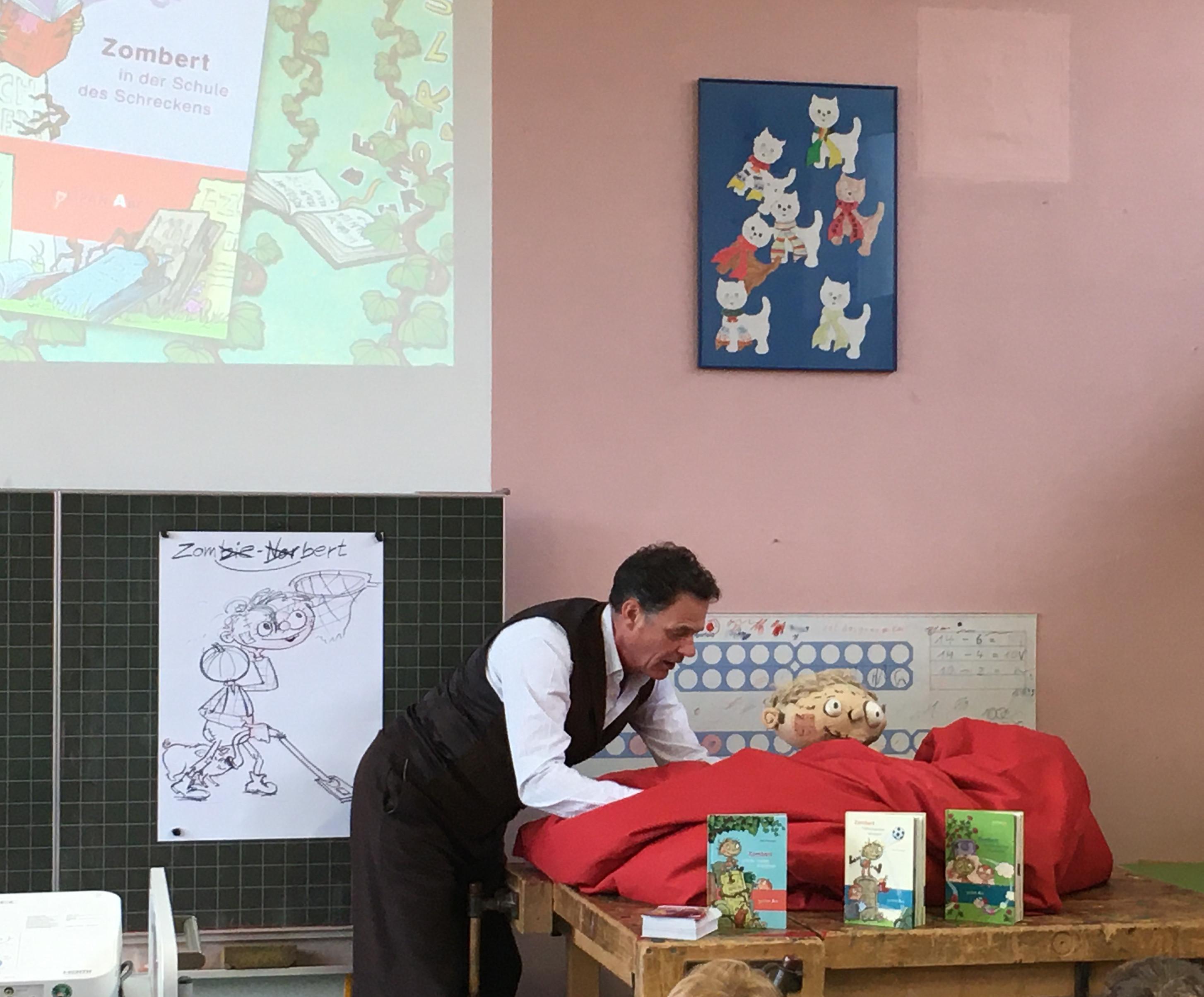 Kai Pannen, Kinderbuchautor, liest in der Grundschule Dertingen aus seinem Buch Zombert und zeigt Zombert-Puppe
