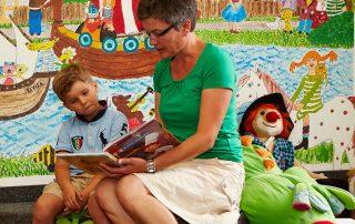 Lesepatin sitzt mit Jungem in Kinderabteilung, liest vor